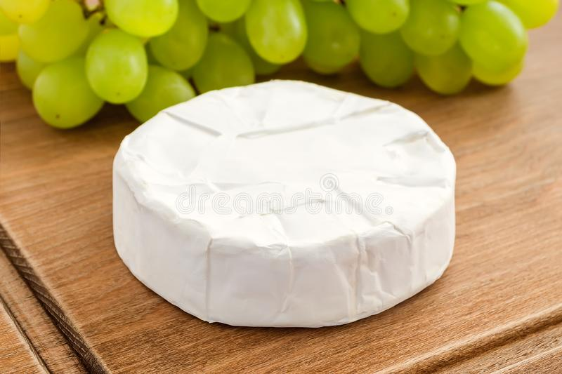Close-up of whole head of camembert and sweet green grapes on a brown wooden cutting board. Soft cheese with edible white mold. Close-up of whole head of stock photography