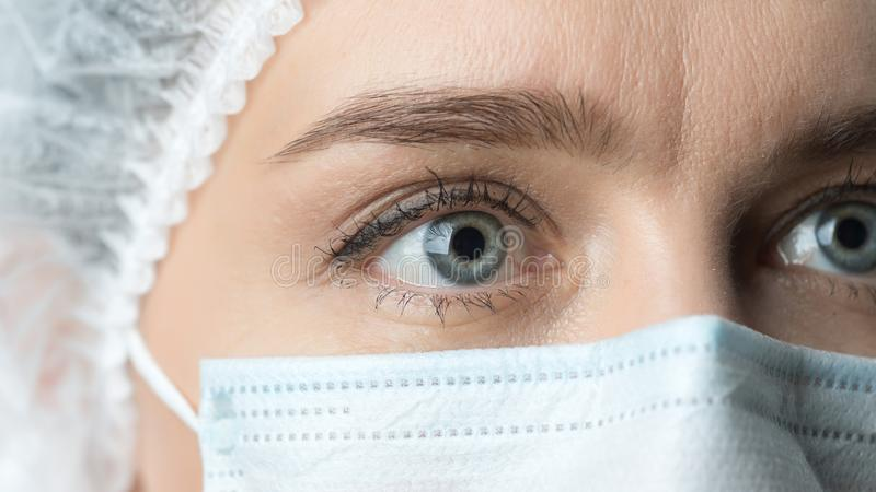 Close up widely opened eyes of doctor. Female doctor in protective mask with beautiful eyes close up. stock images