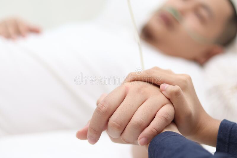 Close up of wife holds hand of her husband who is sick and sleep on bed in hospital, sad emotional moments royalty free stock images