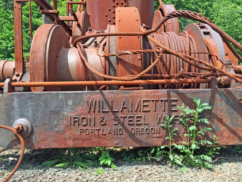 Rusting forestry heavy equipment. Close up of Willamette Iron and Steel Works forestry heavy equipment in field of Oregon on sunny day royalty free stock photo