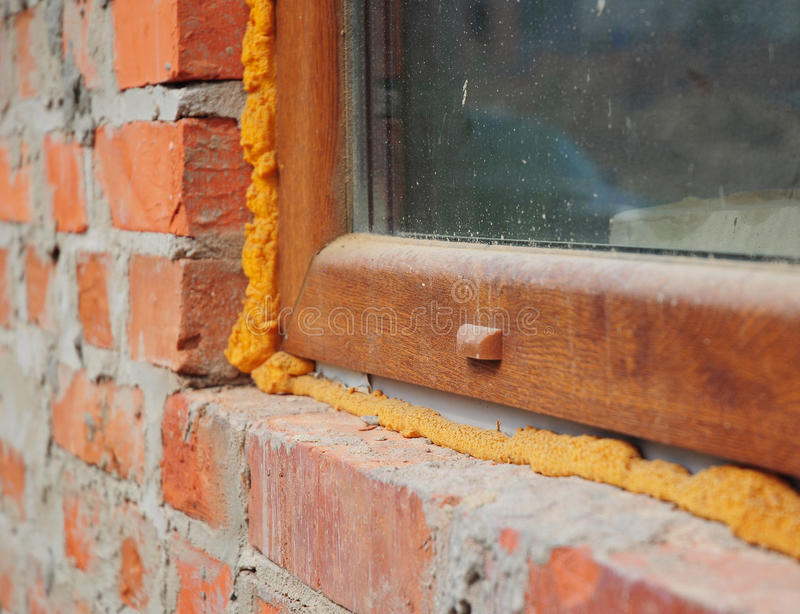 Close up on window insulation with foam. If you replace your windows and doors, you will want to insulate around the opening with spray foam insulation royalty free stock photo