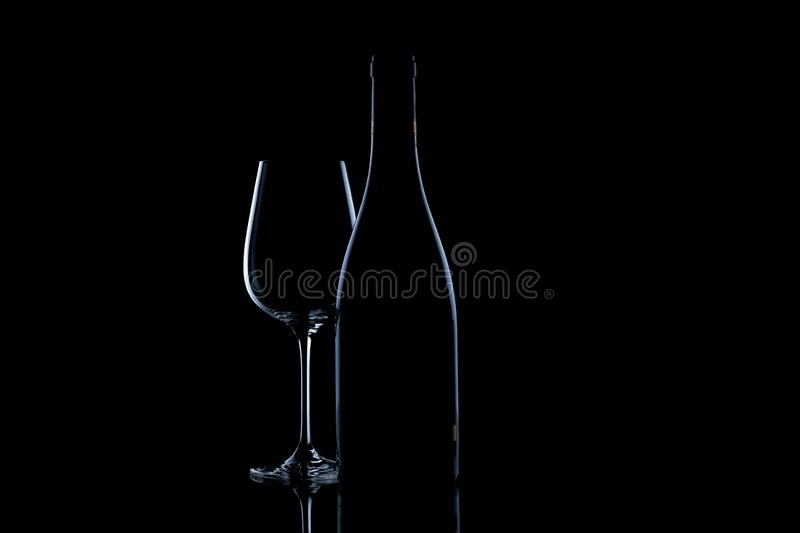 Close-up of wine bottle silhouette and a glass on a black background. Close-up of wine bottle silhouette and a glass on isolated on black background royalty free stock photography