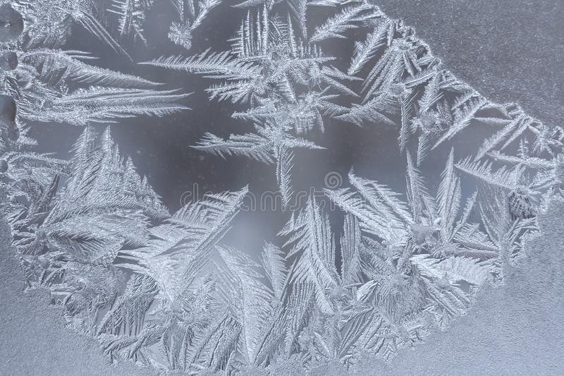 Close-up winter frosty pattern with elongated pointed snowflakes on window . Close-up winter frosty pattern with elongated pointed snowflakes on window stock photos