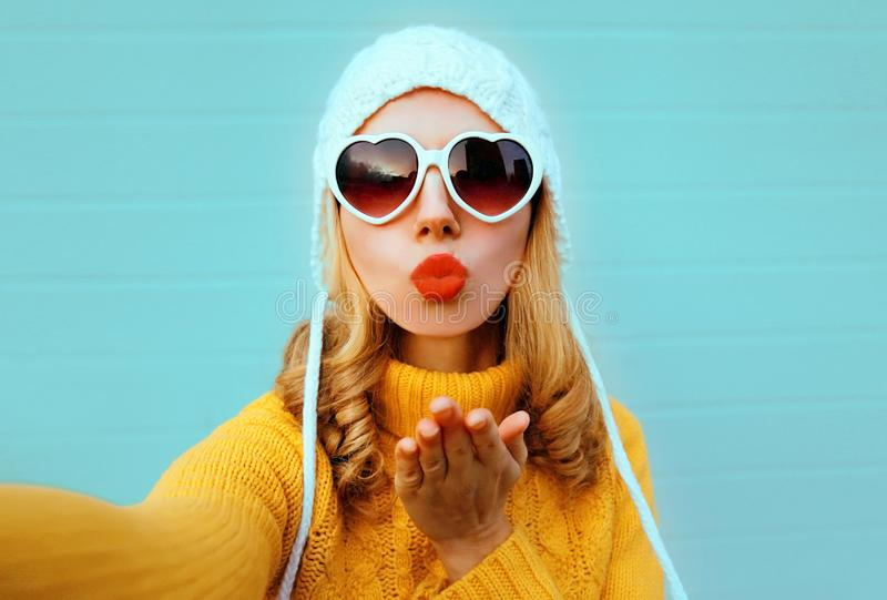 Close up winter portrait pretty woman blowing red lips sending sweet air kiss stretching hand for taking selfie stock photos