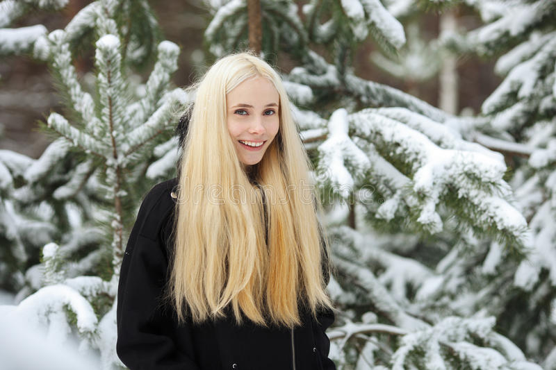 Close up winter portrait: young blonde woman dressed in a warm woolen jacket posing outside in a snowy forest royalty free stock images