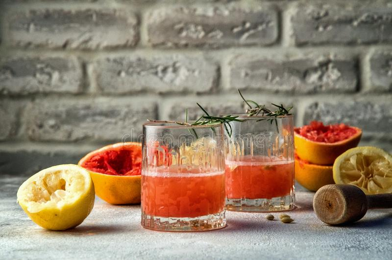 Close up. Winter seasonal vitamins. Homemade citrus lemonade.Two glass glasses filled with red drink. Copy space. Brick wall background royalty free stock photos