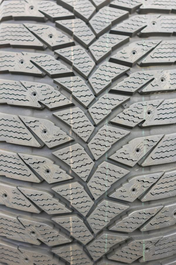 Close-up winter tire tread. Textured tire tread. Part of brand new modern winter car tire. vertical photo.  royalty free stock photos