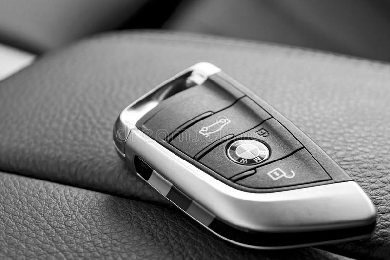 Close up of wireless keys of BMW X5M 2017 in black leather car interior, car interior details. Black and white stock photo