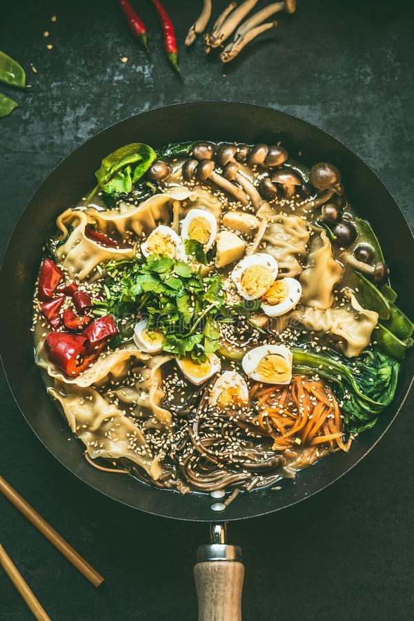 Close up of wok pan with vegetarian  korean hot pot and chopsticks on dark rustic kitchen table background, top view. Copy space. royalty free stock photos