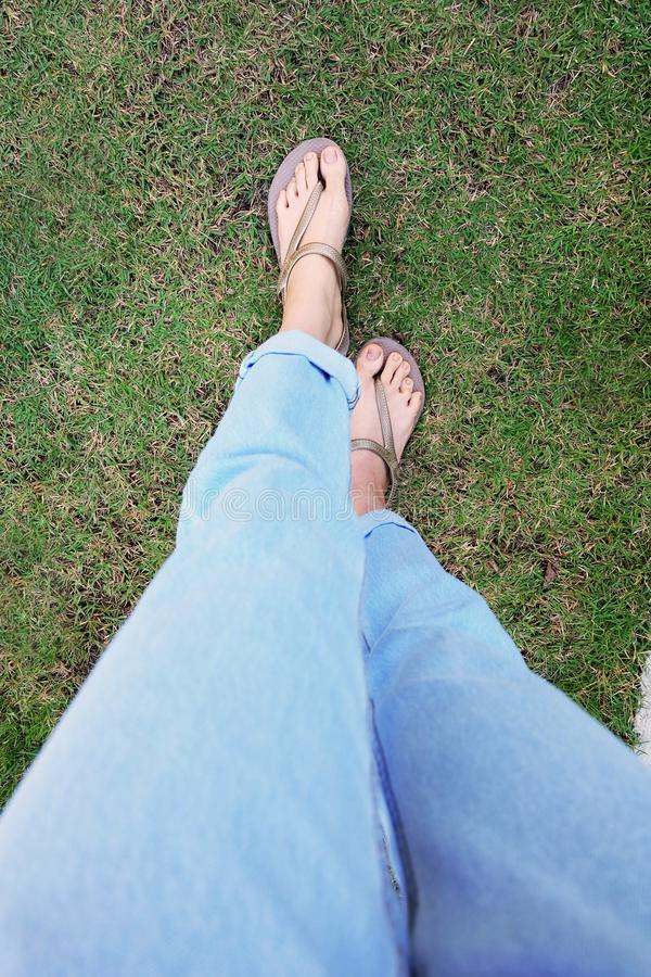 Close Up Woman's Legs and Feet Wearing Flip Flops on the Green Grass. Background Great for Any Use royalty free stock image