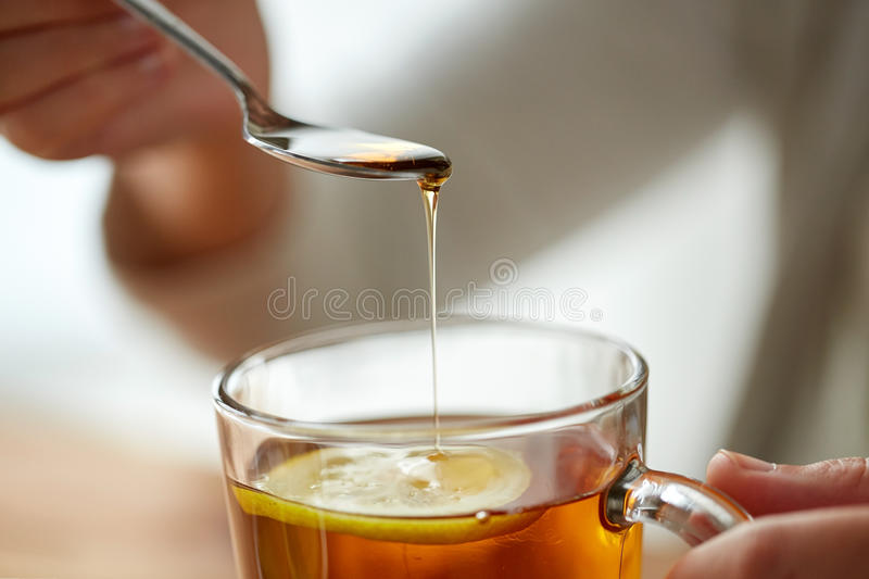 Close up of woman adding honey to tea with lemon royalty free stock image