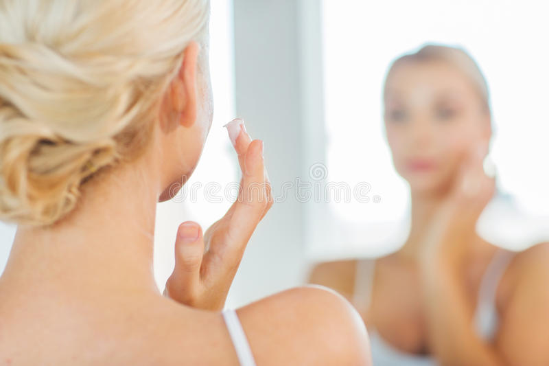Close up of woman applying face cream at bathroom royalty free stock images