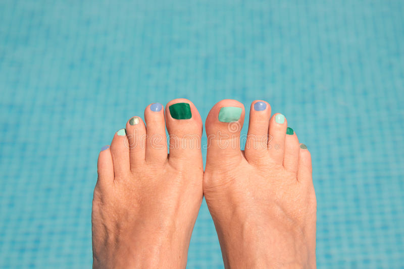 Close up on woman bare feet, blue water. In the background stock images