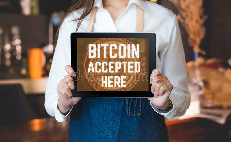 Close up woman barista holding tablet and show bitcoin accepted stock image