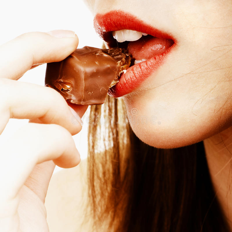 Close up of a woman biting a chocolate bar royalty free stock image