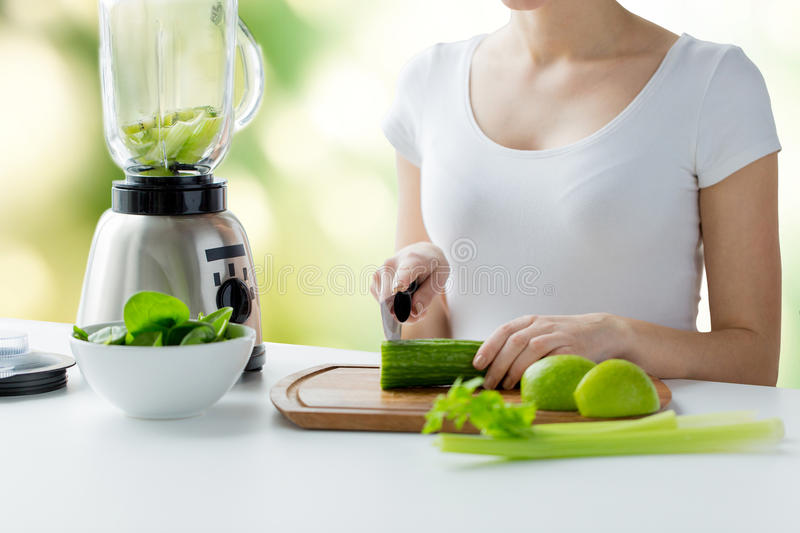 Close up of woman with blender chopping vegetables stock - Green vegetarian cuisine ...