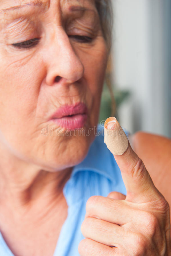 Close up Woman blowing band aid finger wound. Portrait senior woman in pain, hurt and suffering, close up of band aid on injured, cut bloody finger wound royalty free stock photos