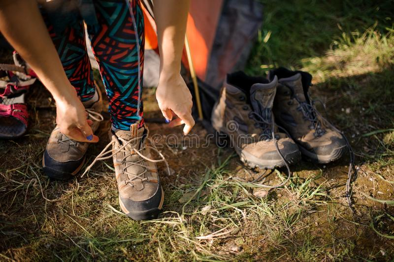 Close-up of woman tying hiking boots near tent. Close-up of woman with blue fingernails tying brown hiking boots near orange tent and another pair of boots stock images