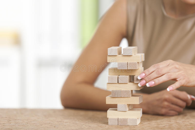 Close up of woman building a tower. Young woman in beige is building a tower from wooden bricks at her workplace in a white office. Concept of a break royalty free stock images