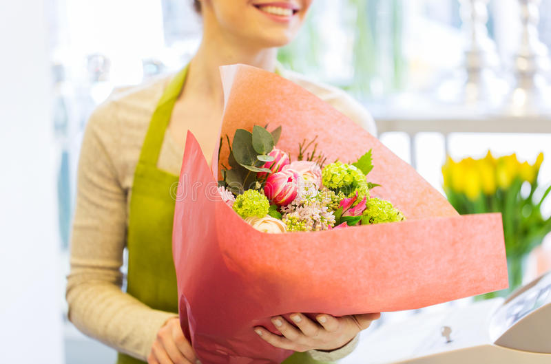 Close up of woman with bunch at flower shop. People, business, sale and floristry concept - close up of happy smiling florist woman holding bunch of flowers royalty free stock photos