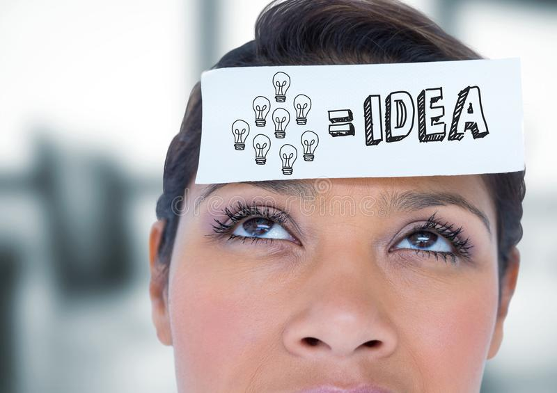 Close up of woman with card on head showing grey idea doodle in blurry grey office royalty free stock photography
