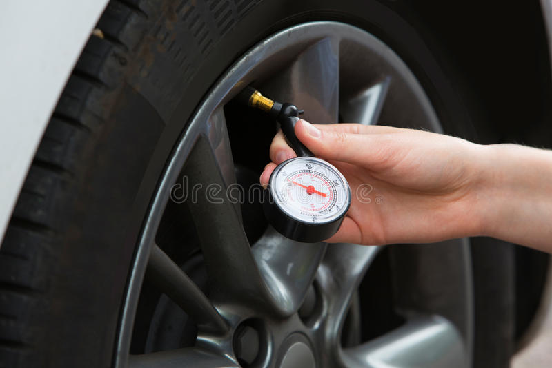 Close-Up Of Woman Checking Car Tyre Pressure With Gauge royalty free stock images