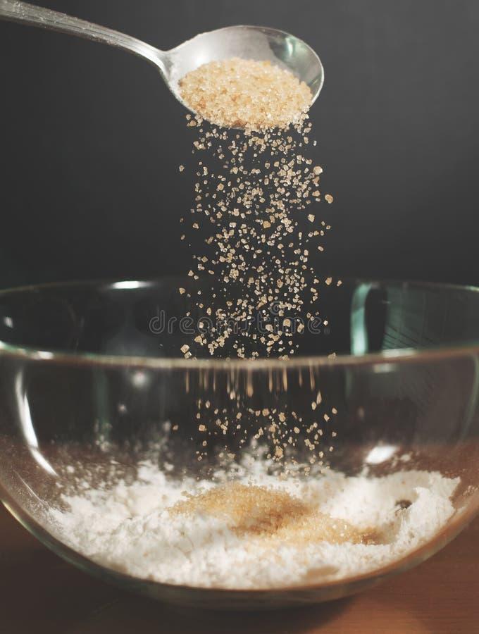 Close up Woman chief sprinkling sugar. Into glass bowl stock photos