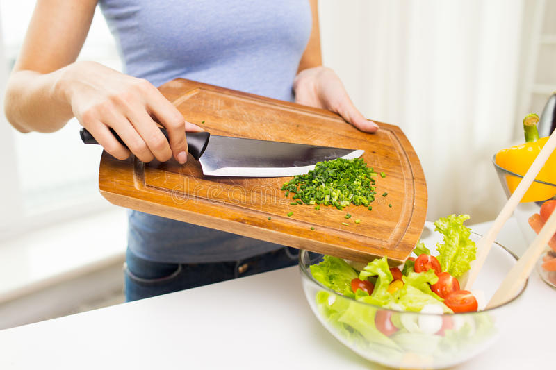 Close up of woman with chopped onion cooking salad royalty free stock photo