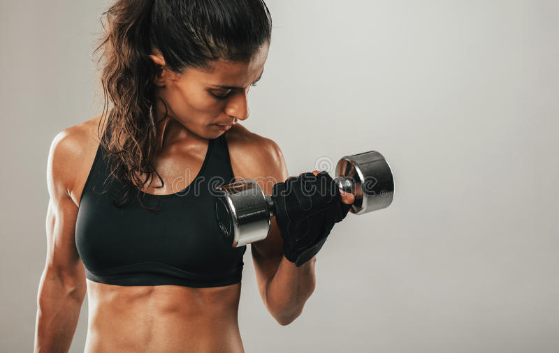 Close up of woman curling dumbbell. Close up of sweating muscular woman with pony tail hair style and short top curling dumbbell over gray background with copy royalty free stock photography