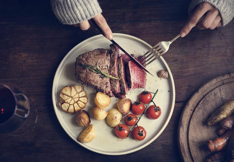 Close up of woman cutting a fillet steak food photography recipe idea royalty free stock images