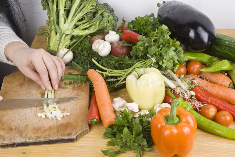 Close up woman cutting vegetables in kitchen royalty free stock photography
