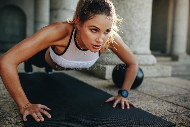 Fitness woman doing push ups on a yoga mat royalty free stock images