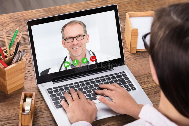 Woman Doing Video Chatting With A Male Doctor royalty free stock photo