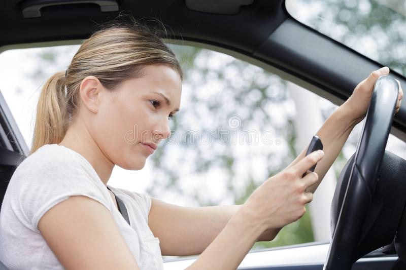 Close-up woman driving and texting royalty free stock image