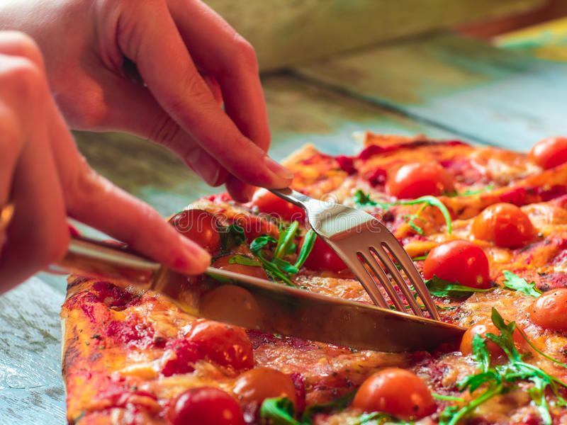 Close up of Woman eating vegetarian pizza in cafe.  royalty free stock photo