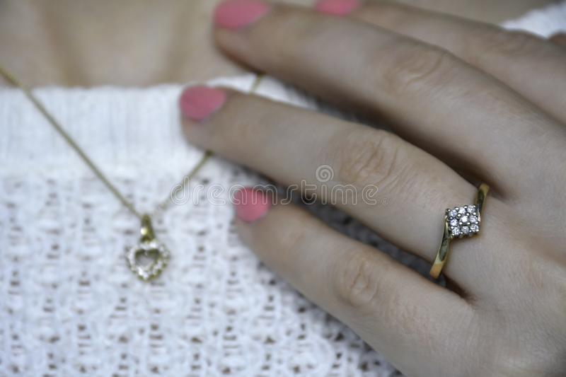 Close-up woman with elegant subtle golden jewelry with diamonds and pink nail polish stock image