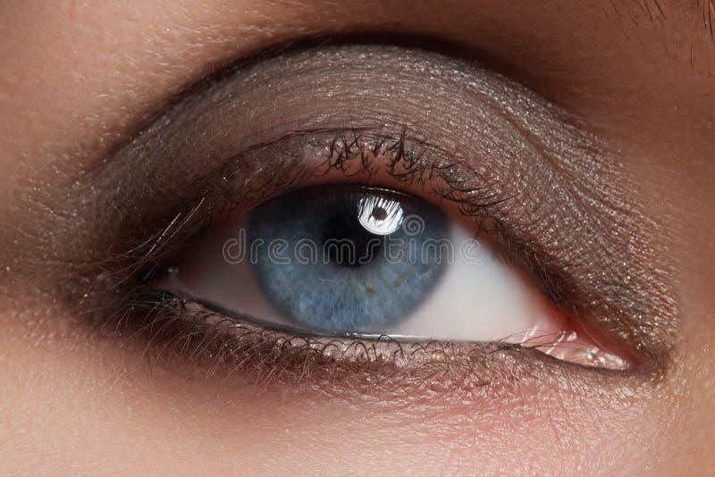 Close-up of woman eye with beautiful brown smokey eyes make-up. Close-up of blue woman eye with beautiful brown shades smokey eyes make-up. Modern fashion make stock image