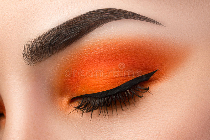 Close-up of woman eye with beautiful orange smokey eyes with black arrow makeup stock photos