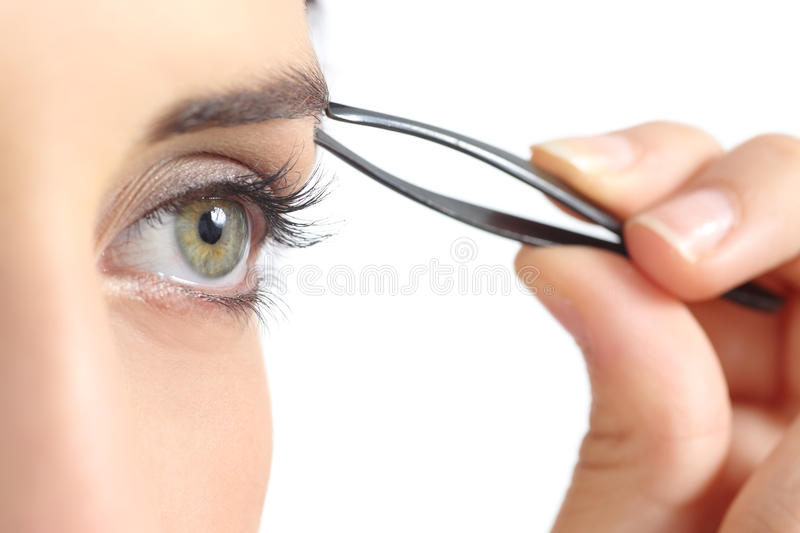 Close up of a woman eye and a hand plucking eyebrows royalty free stock photo