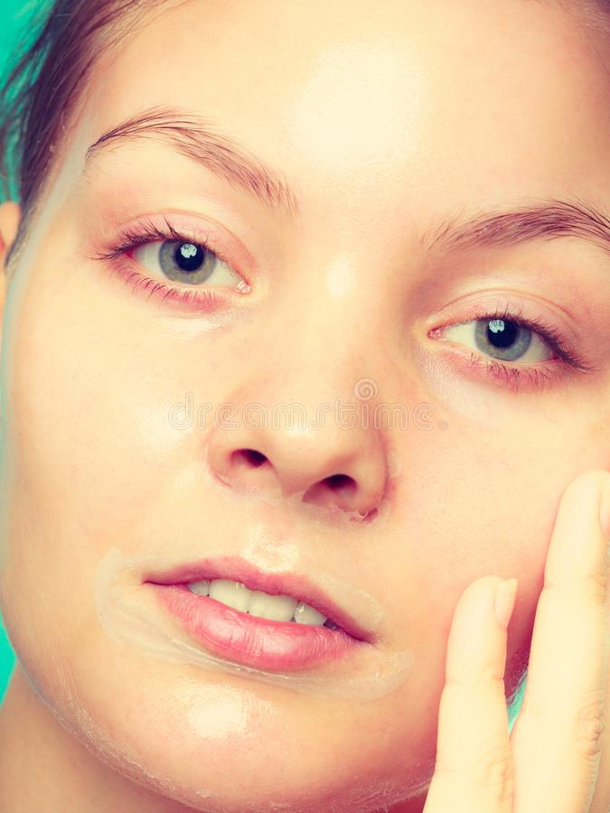 Close up woman in facial peel off mask. Close up young woman in facial peel off mask. Peeling. Beauty and skin care stock image