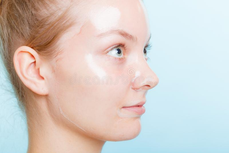 Close up woman in facial peel off mask. Close up young woman in facial peel off mask. Peeling. Beauty and skin care. Side view royalty free stock photography