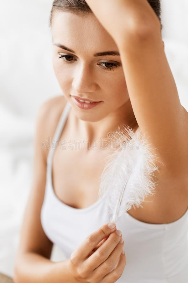Close up of woman with feather touching her armpit royalty free stock image