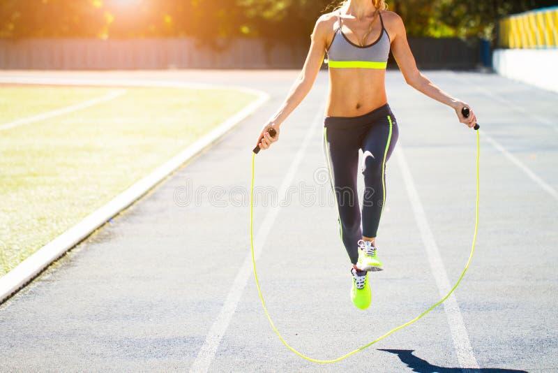 Close up of woman feet jumping, using skipping rope in stadium. Close up of fitness-woman feet jumping, using skipping rope in stadium stock images