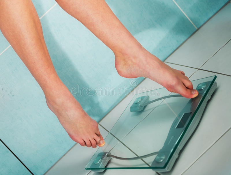 Close up of woman feet weighing in bathroom stock photography