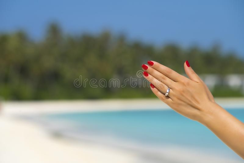 Close up of woman finger showing engagement ring on the tropical beach. Concept of people relationship, ring present, love  and royalty free stock image
