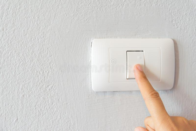 Close up of woman finger turning on light switch royalty free stock image