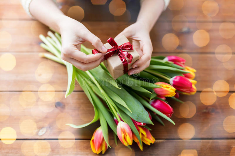 Close up of woman with gift box and tulip flowers stock photo