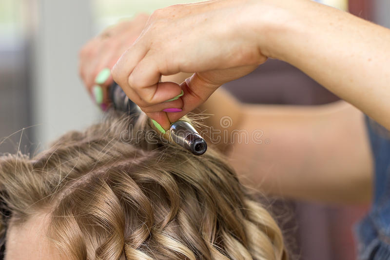 Close-up of a woman hairdresser making curls stock photos