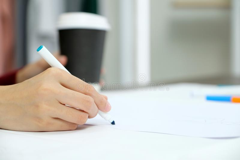 Close up of woman hand holding blue pen over white paper on table desk background stock photography