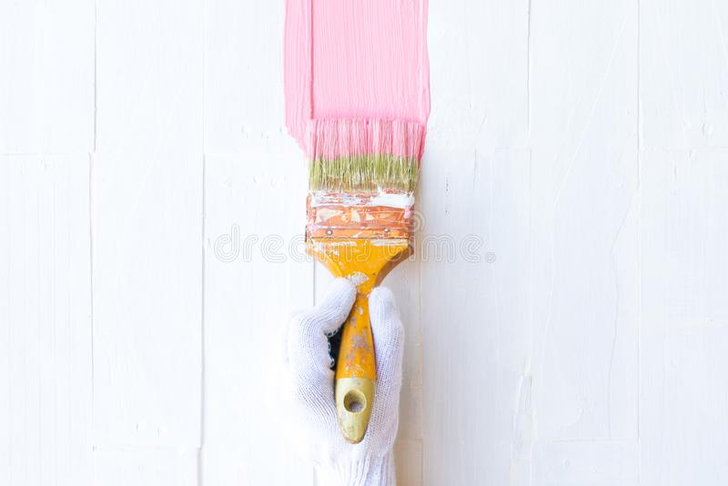 Close up woman hand holding brush painting pink color royalty free stock photography